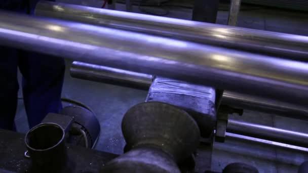 Hände arbeiten auf dem Hintergrund von Edelstahlrohren in der Fabrik.