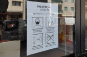 Sign in store window during COVID-19 outbreak in Portugal. Text in Portuguese saying Prevention COVID-19. We appreciate your cooperation. Mask use is obligatory. Disinfect hands.