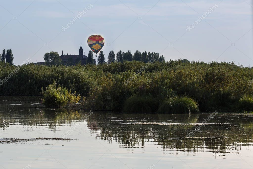 Colorful Hot-Air Balloon in the Sky over Vegetation near Italian Church Tower.
