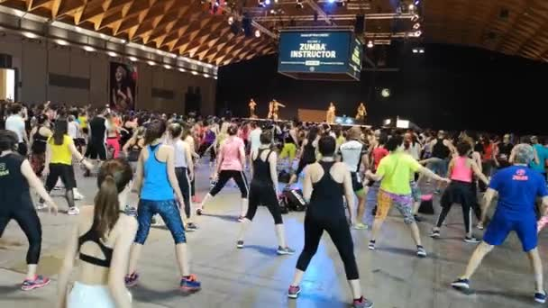 Rimini, Italy - june 2019: Fitness Workout in Gym - People doing Zumba Exercises during Public Event with Music and Teacher on Stage