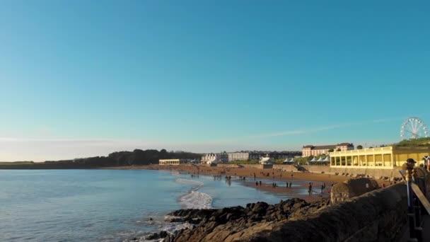 Perfektní slunečný den na pláži Barryho Ostrova v zimě. Rodiny si užívají pláž a promenádu. Blues nebe a klidné moře, ideální místo pro rodinné chvíle u moře.