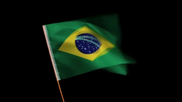 The national flag of Brazil on a wooden pole, fluttering in the wind, on a black background