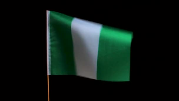 The national flag of Nigeria on a wooden pole flutters in the wind, on a black background