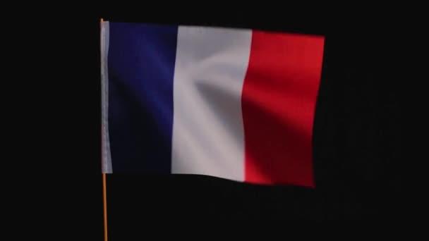 Francouzská národní vlajka vlaje ve větru na černém pozadí