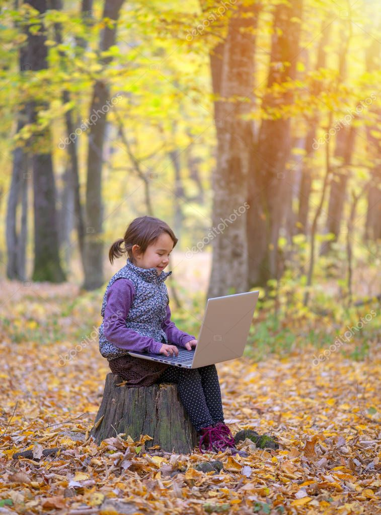 beautiful little girl stands on a trunk of tree smiling and chating at laptop