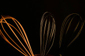 Blick auf drei isoliert glänzende Drahtbesen-Schlaufen, schwarzer Hintergrund (Fokus auf die Mitte))