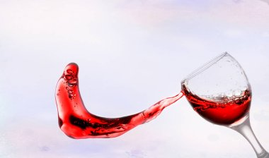 red wine splash from glass on bokeh background