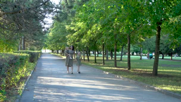 a pregnant mother with two daughters walks in a green Park