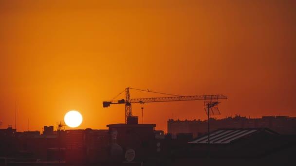 Naplemente a város felett, a nap egy daru mellett megy le a horizonton, és tiszta az ég. Narancssárga tónusok.