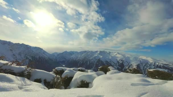 Scenic timelapse alpine landscape with sky and mountain ranges. Snow-capped mountain tops and the clouds are floating in the background. National park of Kyrgyzstan. Nice view.