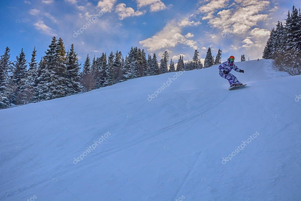 Young man snowboarder running down the slope in Karakol mountains