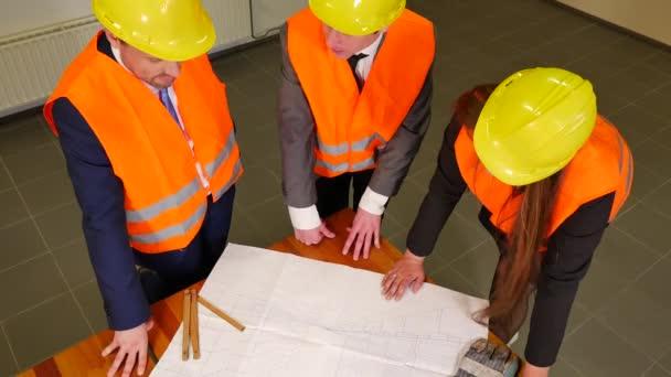 Team aus drei Architekten in Helmen diskutiert Projektplan