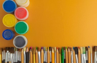 Collage of pencils and paints. Pencils and paints for drawing. The composition of pencils and paints. Brushes and pencils on the table. Drawing set