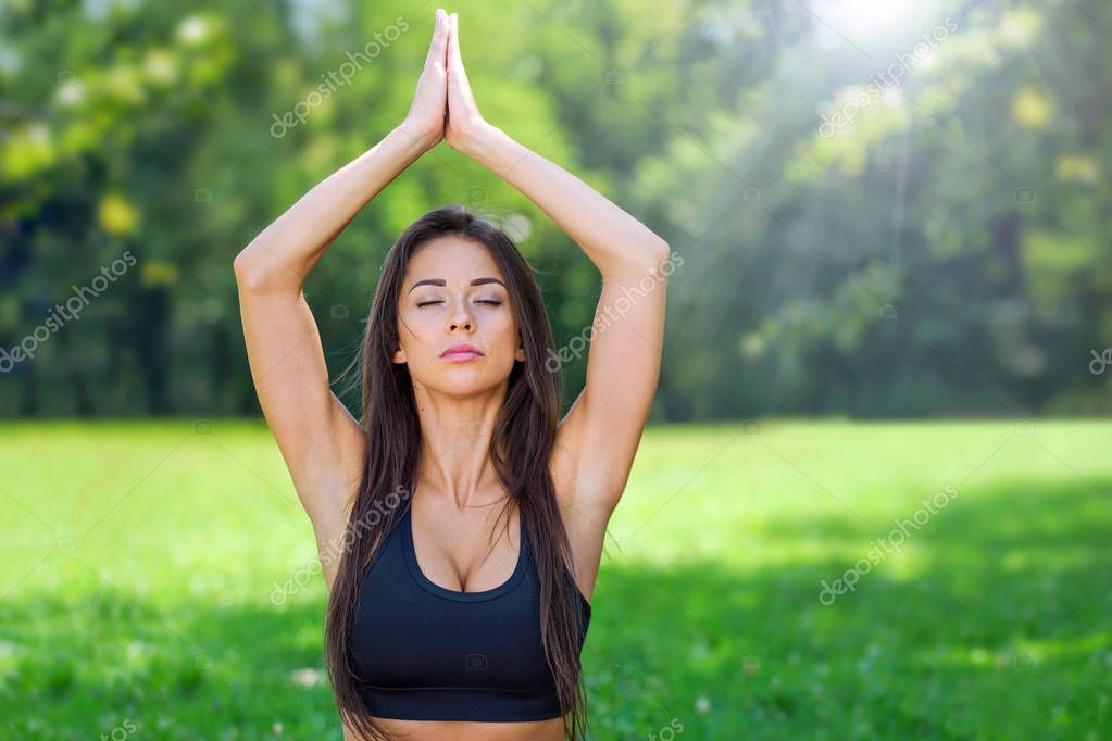 Portrait of attractive and young woman with close eyes doing outdoors yoga meditation in a park on a sunny day