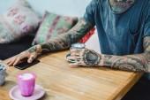 Fotografia mani tatuate. mani che tengono un bicchiere con caffè