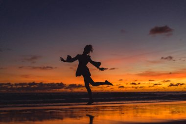 girl is jumping against the backdrop of the setting sun.
