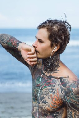 tattooed man with headphones against the blue sky on the ocean.