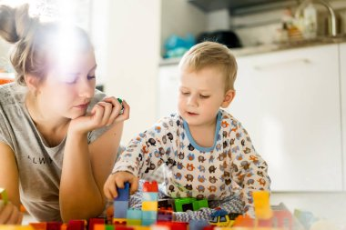 boy child playing with his mother in color children's building kit. The details of the children's building kit are scattered on the floor.