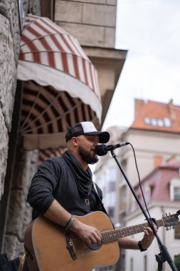 Street musician. A man plays the guitar and sings into a microphone on a city street.