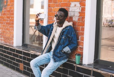 Happy smiling african man taking selfie picture by smartphone sitting with coffee cup on city street