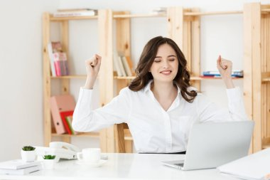 Portrait of smiling pretty young business woman sitting on workplace