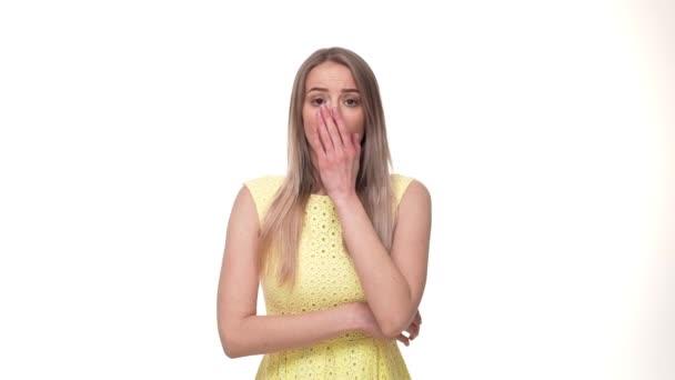 Nahaufnahme einer schockierten Frau, die ihren Mund über weißem Hintergrund bedeckt
