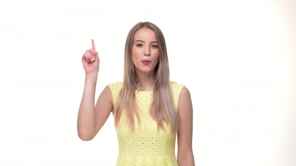 Young attractive woman pointing finger up and looking at camera against white background