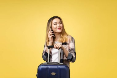 Portrait of happy asian female traveler with suitcase and looking at cellphone against isolated yellow background