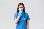 Covid-19, megelőzés vírus, egészségügyi dolgozók és karantén koncepció. Dühös nővér kék köpenyben, orvosi maszk, figyelmeztetés, halkabban, csendesebben, csendesebben, a kamera előtt.
