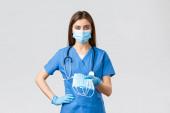 Covid-19, megelőzés vírus, egészségügyi dolgozók és karantén koncepció. Fiatal orvos vagy női ápolónő kék köpenyben és a koronavírus-fertőzés elleni védőfelszerelés, adjon orvosi maszkot