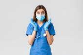Covid-19, megelőzés vírus, egészségügyi dolgozók és karantén koncepció. Meglepett és sokkos női ápolónő kék köpenyben és orvosi maszkban, ziháló tekintet csodálkozó kamera