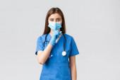 Covid-19, megelőzés vírus, egészségügyi dolgozók és karantén koncepció. Halkabban. Komoly női ápolónő kék köpenyben, orvosi maszk és kesztyű, pszt, szorítsa ujját az ajkakhoz