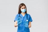 Covid-19, megelőzés vírus, egészség, egészségügyi dolgozók koncepciója. Nem, köszönöm. Elégedetlen és vonakodó ápolónő vagy orvos orvosi maszkban és műtősköpenyben, állítsa meg, utasítsa el vagy utasítsa el a jelet