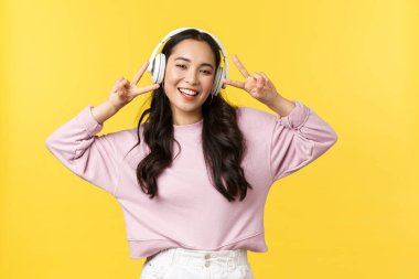 People emotions, lifestyle leisure and beauty concept. Enthusiastic and happy pretty asian woman feeling joyful as listening music in wireless earphones, showing peace sign