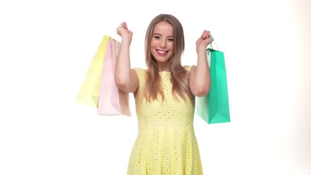 krásná mladá žena s úsměvem a držení s barevnými nákupními taškami na bílém pozadí