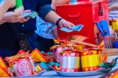 Photo People buying paper money ,paper gold and joss stick sets at Chinese shrine for making merit and pay respect to god in Chinese New Year day may life be blessed with health and happiness all through.