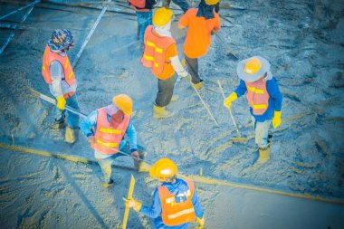 Concreting workers are leveling poured liquid concrete on a steel reinforcement to form strong floor slabs.
