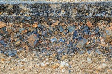 The layer of asphalt road with soil and rock after landslide.