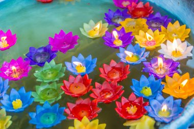 Colorful lotus flower with burning candles are floating on the water to worship the Buddha with pray blessings at at Wat Rong Suea Ten Temple, also known as the Blue Temple, Chiang Rai, Thailand.