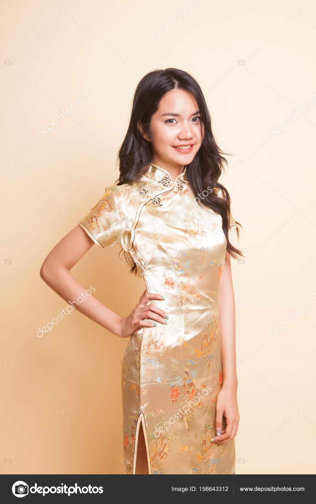 70ddfd592105 Portrét Asian girl v zlaté čínské cheongsam šaty na béžové pozadí– stock  obrázky