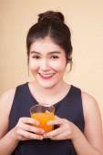 Mladá asijská žena bod pomerančový džus na béžové pozadí