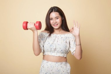Healthy Asian woman show OK with dumbbells on beige background