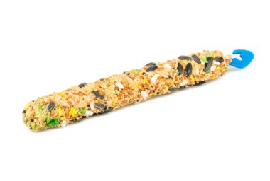 Food for parrots with various cereals on a stick on a white background