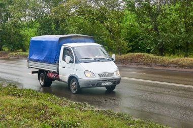 Krasnoyarsk, Russia - July 30, 2018: GAZ 3302 Gazelle with an awning passing on the wet road to a rain.