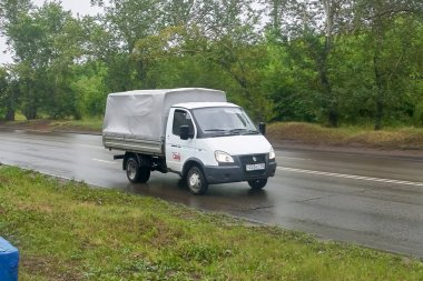 Krasnoyarsk, Russia - July 30, 2018: GAZ 3302 Gazelle with an awning passing on the wet road to a rain .