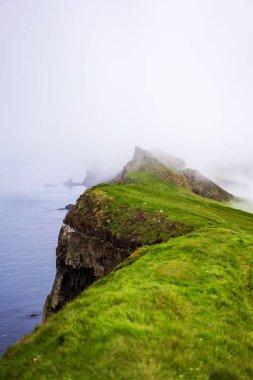 Foggy landscape of green cliffs above the ocean. Mykines, Faroe Islands.