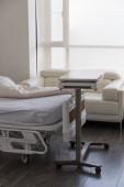 kórházi hordágy fehér lepedővel, kanapéval és egy guruló asztallal az ablak mellett