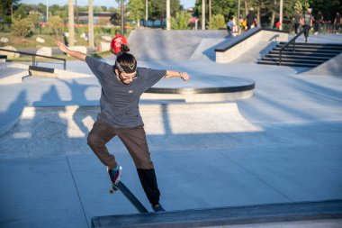 Detroit, Michigan, USA - 08.09.2019: Skaters practicing their tricks at sunny day in Detroit urban skate park
