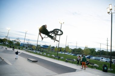 Detroit, Michigan, USA - 10.10.2019: Bikers and skaters practice tricks at dusk in Detroit