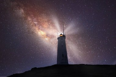 old lighthouse with the milky way galaxy in the night